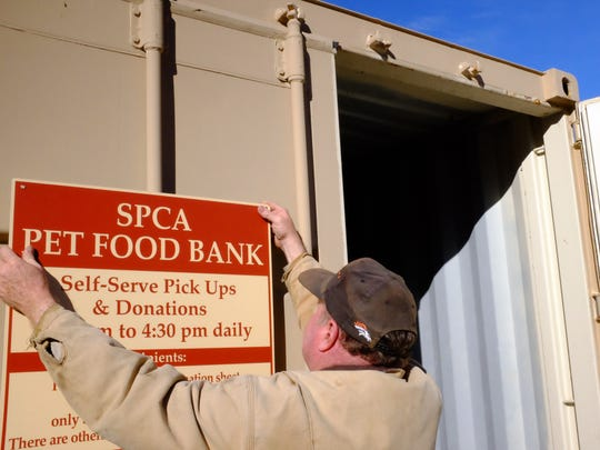 The SPCA's Randy Farmer puts up a new sign on the Pet Food Bank on Tuesday.