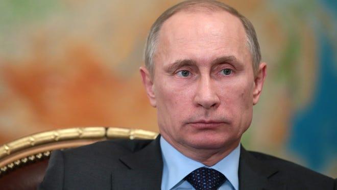 Russian President Vladimir Putin listens during a meeting on Feb. 26, 2014.