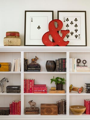This undated photo provided by Betsy Burnham shows a room by California-based designer Betsy Burnham, with framed prints of playing cards by William Wegman that are propped up to form a whimsical backdrop for other decorative items. The days after guests have gone home and holiday decorations have been put away can be perfect for rethinking and changing the location of framed items in your home.