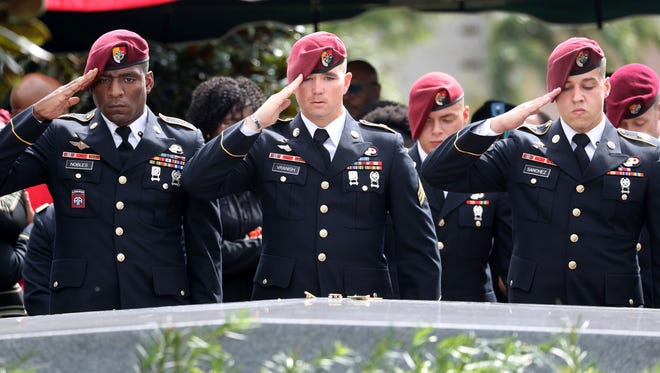 Members of the 3rd Special Forces Group Airborne 2nd Battalion leave pins and salute the casket after the burial of Army Sgt. La David Johnson at the Hollywood Memorial Gardens in Hollywood, Fla., on Oct. 21, 2017.