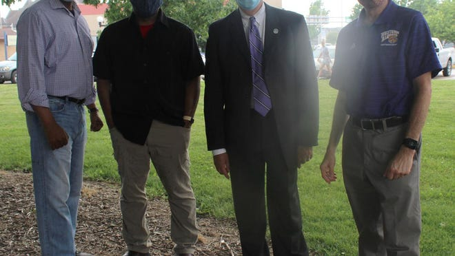 Left to right: Dr. Sterling Saddler, Ronald Pettigrew, Mayor Inman, and Dr. Abraham stand under a tree in Chandler Park to avoid the rain.