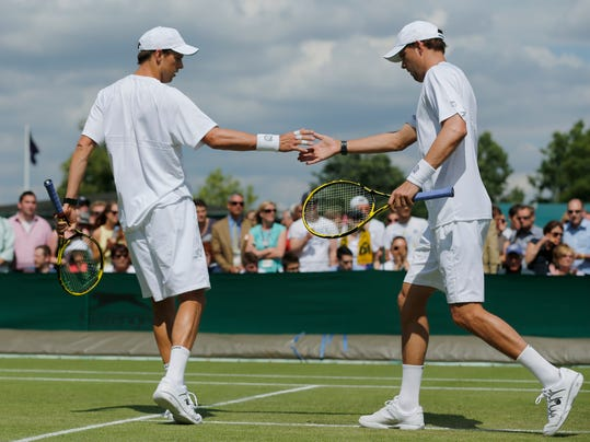 Mike Bryan, left, and Bob Bryan both of the U.S. touch hands as they play a men's doubles match against Matthew Ebden of Australia and Samuel Groth of Australia plays at the All England Lawn Tennis Championships in Wimbledon, London, Friday, June 27, 2014. (AP Photo/Ben Curtis)