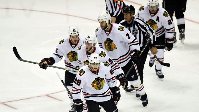 Chicago Blackhawks right wing Patrick Kane (88) skates back towards the bench with his linemates after scoring a goal during the second period.