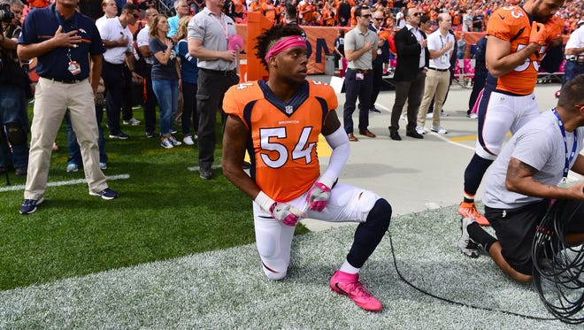 Denver Broncos inside linebacker Brandon Marshall (54) kneels during the national anthem before the start of the game against the Atlanta Falcons at Sports Authority Field at Mile High.