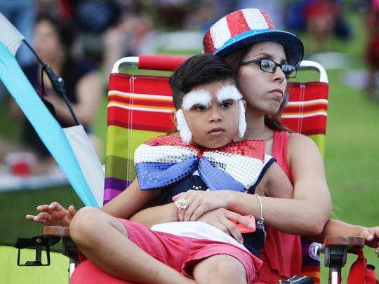 Nancy Islas holds her son, Jay Garcia, 7, as they sit and soak in the Fourth of July festivities Saturday at Tom Brown Park.
