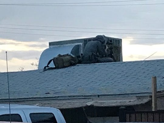 A sniper sits on an adjacent home several yards away