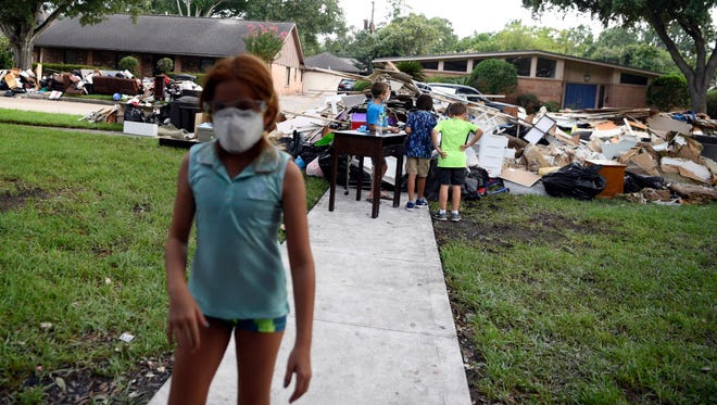 Dry wall, furniture and carpets sit outside of Staci Beinart's home after flooding from Hurricane Harvey damaged the Meyerland neighborhood. The Beinart family was rescued by Nick Sissa, who happened to be driving paramedics around in his military vehicle when they were called to help Beinart's nine-year-old son who was having an asthma attack.
