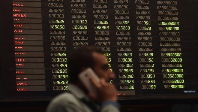 A Pakistani stockbroker walks past an index board showing share prices during a trading session at the Pakistan Stock Exchange (PSX) in Karachi on Feb. 6.