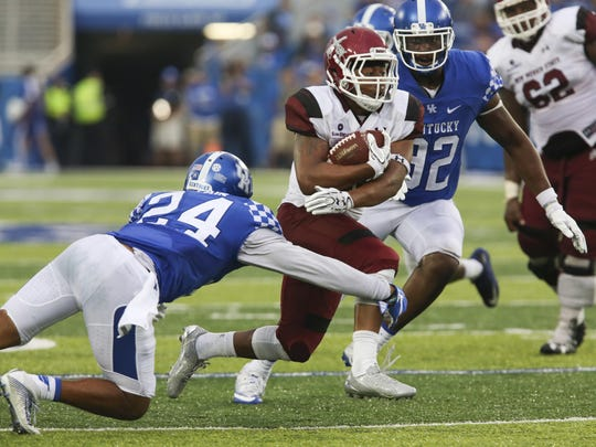 New Mexico State running back Xavier Hall, center, splits Kentucky defenders Blake McClain, left, and Alvonte Bell, right, in the second half of an NCAA college football game Saturday, Sept. 17, 2016, in Lexington, Ky. (AP Photo/David Stephenson)