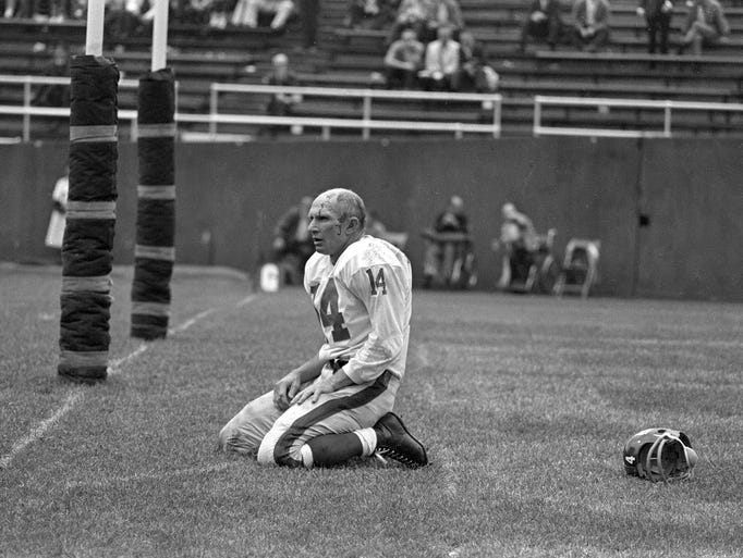 New York Giants quarterback Y.A. Tittle squats on the