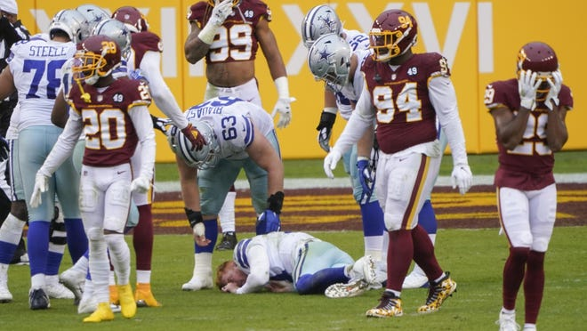 Players react to seeing Dallas Cowboys quarterback Andy Dalton lying on the ground after getting hit by Washington Football Team linebacker Jon Bostic  in the second half of Sunday's game. Dalton did not return.