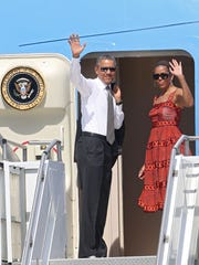 President Barack Obama and Michelle Obama wave before boarding Air Force One to depart Palm Springs on June 16.