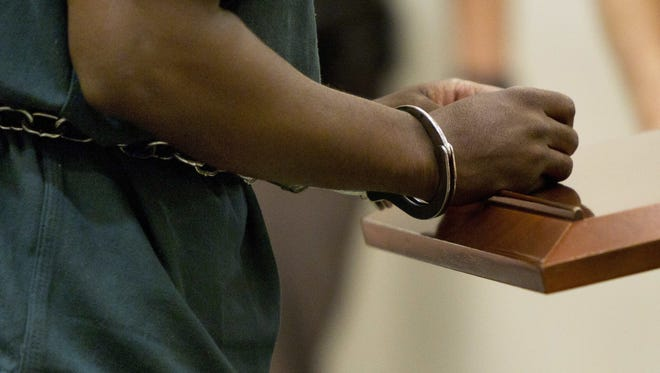 """In this Friday, Sept. 30, 2016 photo, Ahmad Williams wears handcuffs as he appears for his resentencing hearing at the Kent County Courthouse in Grand Rapids. Williams, who was convicted in the 1988 fatal shooting of Derrick Pimpleton, is one of several """"juvenile lifers"""" to be resentenced because of Supreme Court rulings that ended mandatory no-parole sentences for crimes committed by juveniles."""