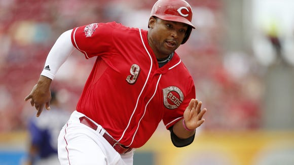 Reds left fielder Marlon Byrd rounds third base and