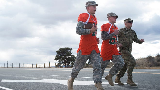 Army ROTC cadets from CSU run the game ball along U.S. Highway 287 to the Wyoming border before the 2015 Border War football game. The CSU cadets pass the ball on to Wyoming ROTC members in a ceremonial exchange at the border that will celebrate its 50th year Friday.