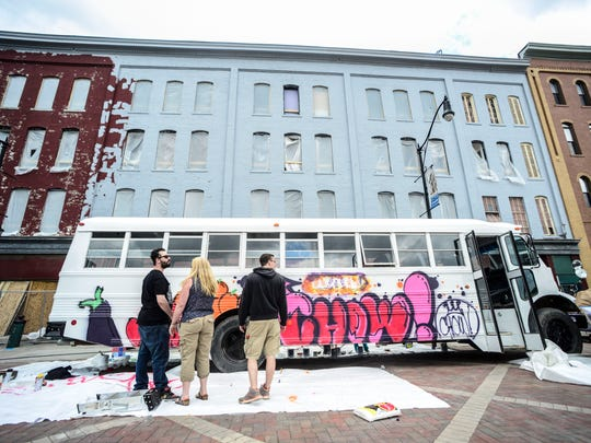 Local artist and volunteers gather at the Riverwalk in downtown Binghamton to help paint the CHOW Bus during Mural Fest 2014.