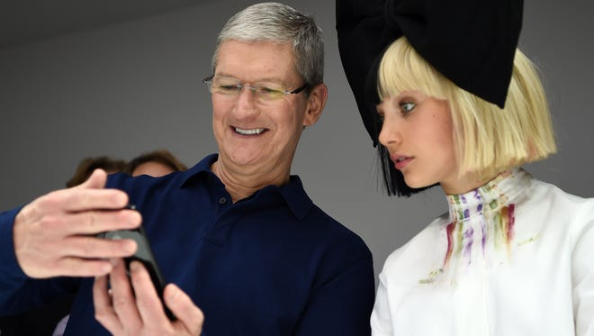 Apple CEO Tim Cook (L) shows dancer Maddie Ziegler (R) a new iPhone during a product demonstration at Bill Graham Civic Auditorium in San Francisco, California on September 07, 2016.