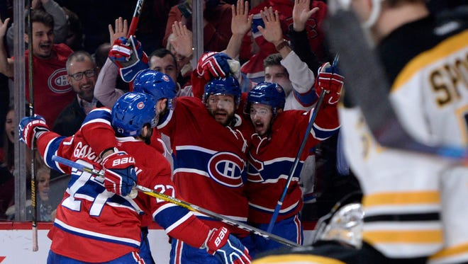 Canadiens forward Paul Byron (41) is congratulated by teammates after scoring a goal against Bruins in the third period.