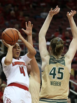 U of L's Mariya Moore, #4, tries to shoot against USF's Katelyn Weber, #45, during their game at the KFC Yum! Center.