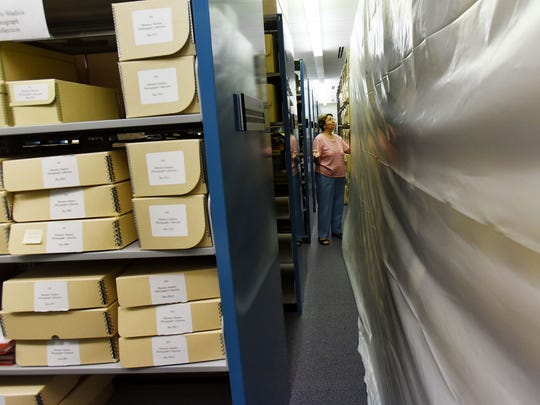 Dominique Carriere has worked at the LSUS archives for 25 years. She shows the protective plastic lining in the archives.