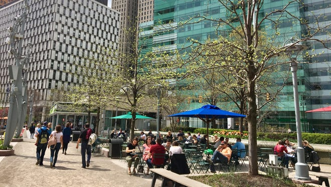 People spend the lunch hour outdoors April 26, 2017 at Campus Martius in downtown Detroit.