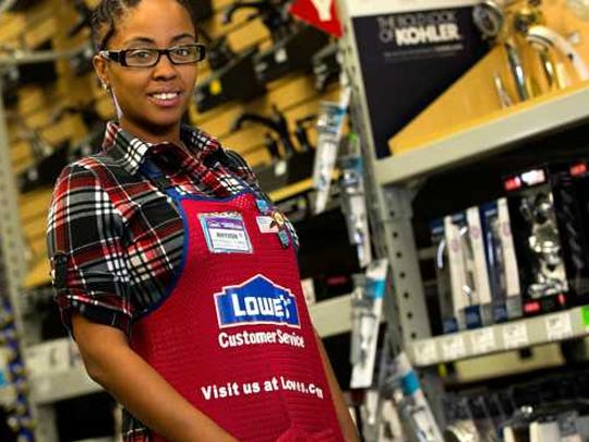 A Lowe's employee stands in an aisle.