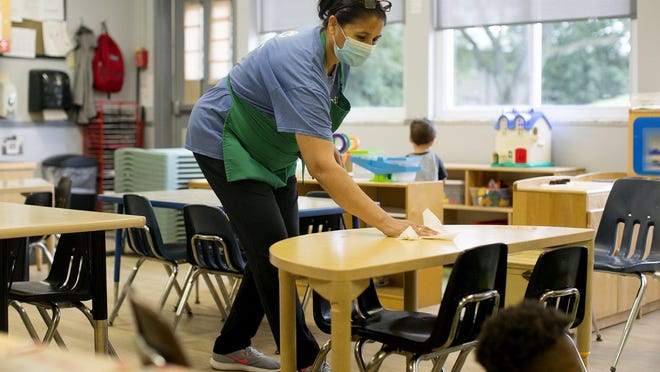 Chandra Dhital, sanitizes tables in the pre-k room, after an activity at Creative Child Care on Thursday, July 30. The center is running at about 40 percent capacity.