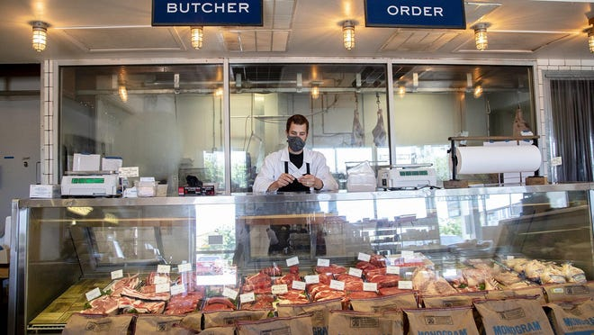 Sam Garrison, lead butcher, places meat in a display at Salt & Time in East Austin.