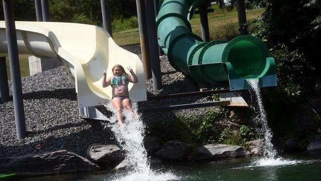Hazel Gatchell slides down a long slide at their family's water park in Epping.
