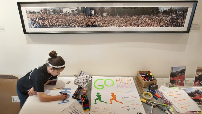 Savannah Rivera makes a sign in support of Marathoners running in 2019 for the Hopkinton Center for the Arts Saturday at the Hopkinton Center for the Arts.