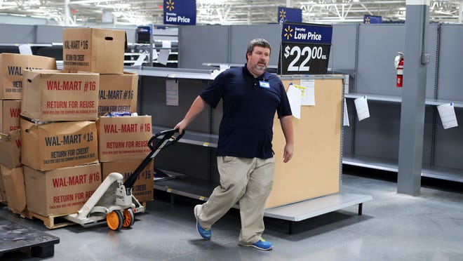 Walmart employee Jonathan Totty takes merchandise to br stocked at the new Walmart on Memorial Boulevard Tuesday, Sept. 23, 2014. The store opened in October 2014.