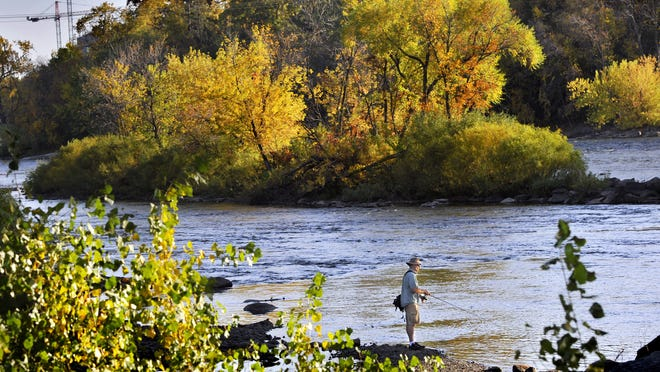 A fisherman tries his luck under the brilliant fall colors surrounding the Mississippi River on Tuesday in Sauk Rapids.