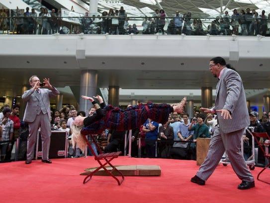 Penn & Teller levitate a woman in a shopping mall to