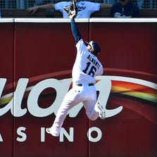 SAN DIEGO, CA - AUGUST 13:  Abraham Almonte #16 of the San Diego Padres makes a leaping catch at the wall to take away a hit from Drew Stubbs #13 of the Colorado Rockies during the first inning of a baseball game at Petco Park on August 13, 2014 in San Diego, California.  (Photo by Denis Poroy/Getty Images)