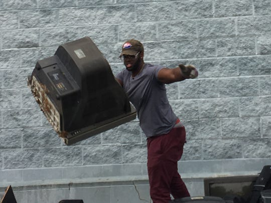 Red Raider Yondel Dudley tosses an old television as he and other Shippensburg University football players sorted electronics after Ship Shape Day in 2017.