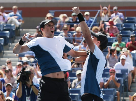 Bob Bryan, right, and brother Mike Bryan celebrate after winning the Men's Doubles championship match of the 2014 U.S. Open tennis tournament, Sunday, Sept. 7, 2014, in New York. (AP Photo/Mike Groll)