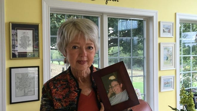 Terri Roberts holds a photo of her son, Charles Carl Roberts IV, who shot and killed Amish girls in their schoolhouse 10 years ago.
