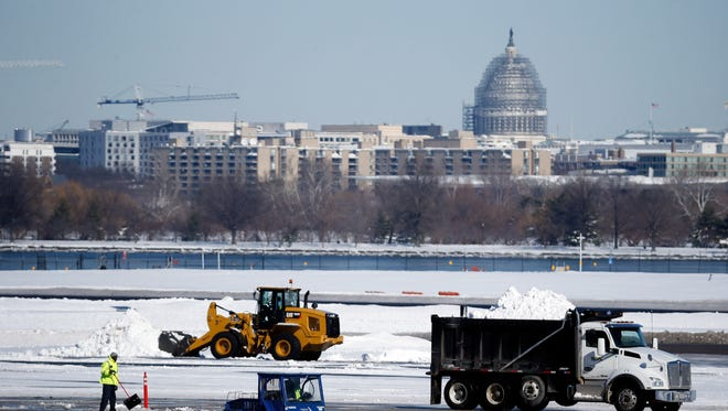 Workers remove snow on from Washington's Ronald Reagan National Airport with the U.S. Capitol dome seen behind on Sunday, Jan. 24, 2016.