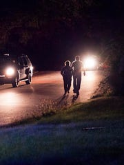 People walk toward the scene of a reported shooting