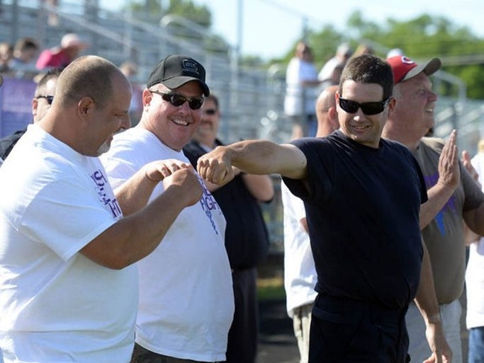 Union County Deputy Shaun Tudor, left, and Liberty Police officer Andrew Jordan, right, fist bump each other before volunteering to be zapped by a Taser during the Union County Relay for Life in Liberty Saturday, June 14, 2014. The pair raised over $1,000 for the American Cancer Society.