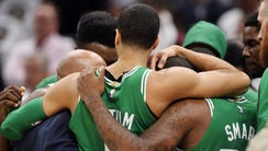Celtics players hold each other after Gordon Hayward's