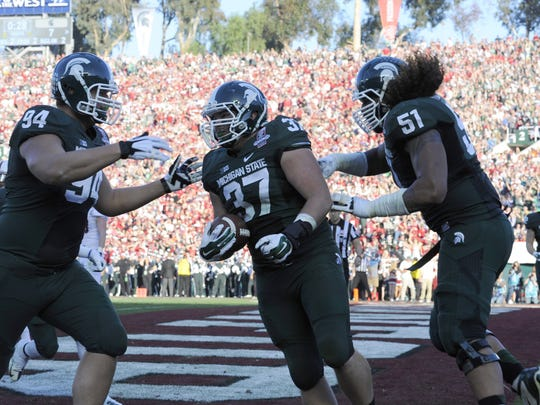 MSU's Trevon Pendleton celebrates his first-half touchdown catch against Stanford with teammates Michael Dennis, left, and Fou Fonoto at the Rose Bowl Jan. 1, 2014.