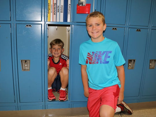 Fox Valley Christian Academy eighth-grade student Joshua Schinschke checks out his locker with his second-grade brother, Eli Schinschke.