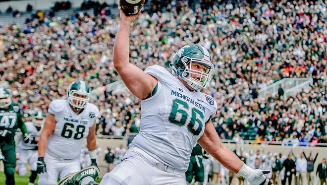 Offensive lineman Jack Allen celebrates scoring a touchdown for the white team in the 1st quarter of the MSU Spring Football game Saturday at Spartan Stadium in East Lansing. This would turn out to be the only touchdown of the game.