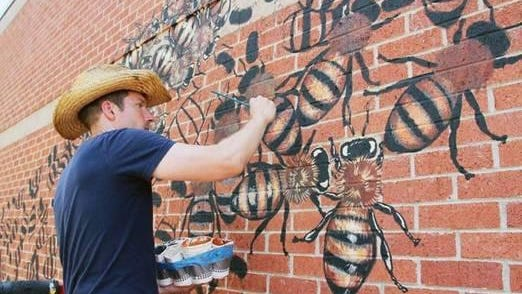Muralist Matthew Willey painting honey bees. Willey will begin painting a similar mural Monday in downtown Hendersonville on the exterior walls of Hands On! Children's Museum. The project will take several weeks, and the public is invited to watch.