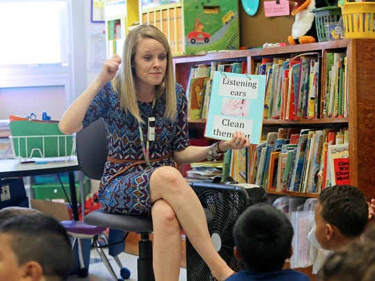 Tori Quinones, a kindergarten teacher at Marbrook Elementary School, reads a book to her students on the second day of school.