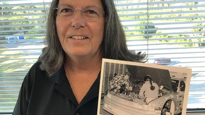 Carmen Moore holds a photograph of herself working on an ARCA stock-car engine in the 1990s.