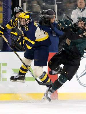 Michigan's Michael Downing (5) collides with MSU's Josh Jacobs during the first period of the Wolverines' 4-1 victory in the Hockey City Classic outdoor game Saturday night at Soldier Field in Chicago.