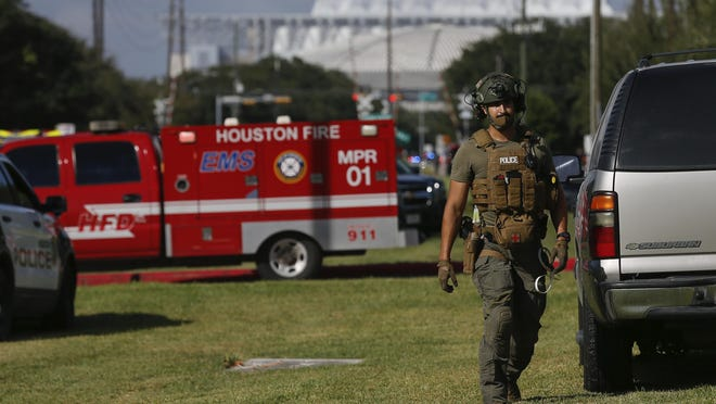 Law enforcement officials at the scene of an officer-involved shooting at an apartment complex  on Tuesday, Oct. 20, 2020, in Houston. Two Houston officers were shot before a SWAT team was dispatched to the scene, where the suspected shooter was arrested, authorities said.
