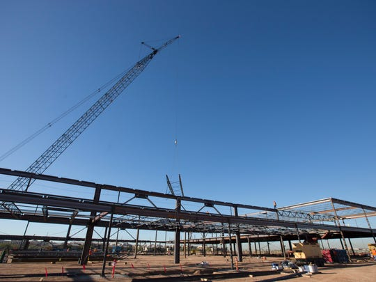 Construction workers erect steel framework for the